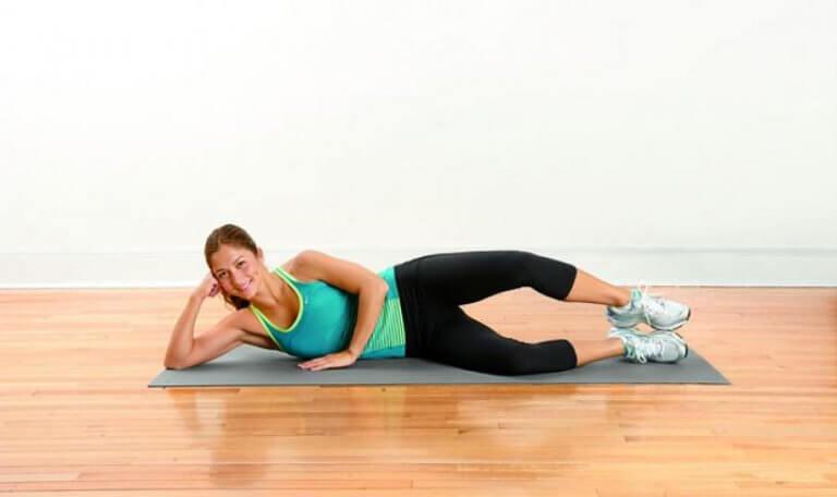 Frau macht Übung gegen Schmerzen in den Beinen