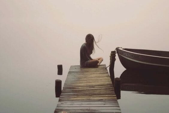 Ein Mädchen sitzt in Stille auf einem Steg am Wasser mit einem Boot.