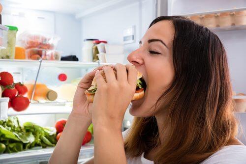 Frau isst Hamburger statt Vorteile von Chiasamen zu genießen