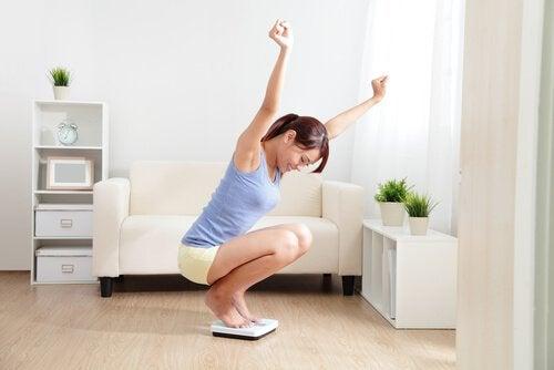 Tägliches Spazierengehen hilft beim Abnehmen, was die junge Frau auf der Waage überprüft