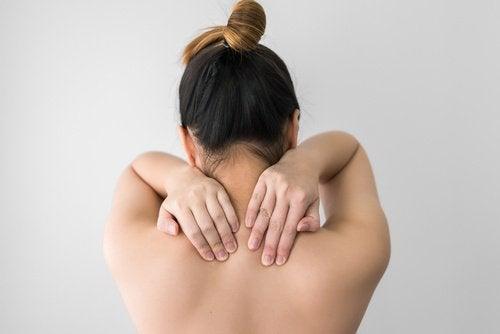 Frau hat sich mit nassen Haaren ins Bett gelegt und leidet jetzt an Muskelschmerzen