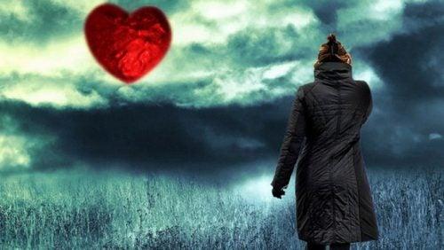 Eine Frau sieht ein rotes Herz am Horizont. Innerer Frieden ist nah.