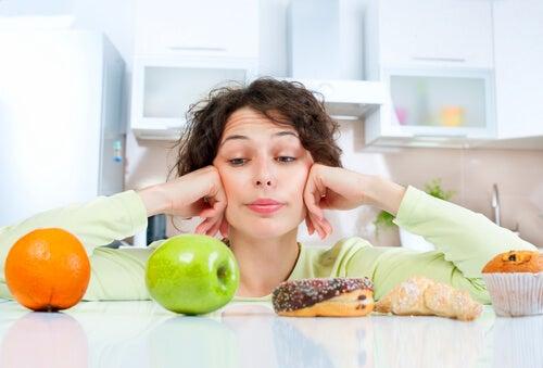 Frau sucht Gründe für brüchige Fingernägel: ungesunde Ernährung