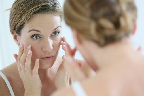 Linien auf den Nägeln einer Frau, die in den Spiegel blickt