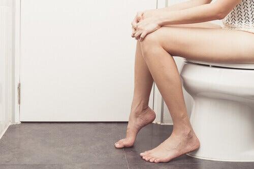 Frau auf der Toilette weiß, dass heller Stuhlgang auf Krankheit hinweist