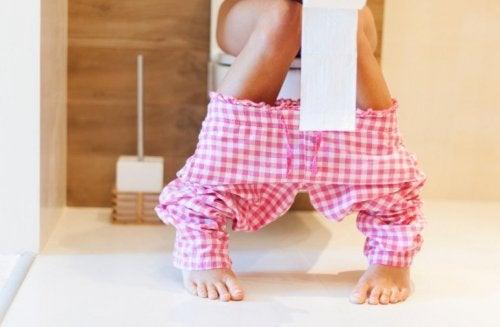 Frau auf der Toilette untersucht Stuhlgang