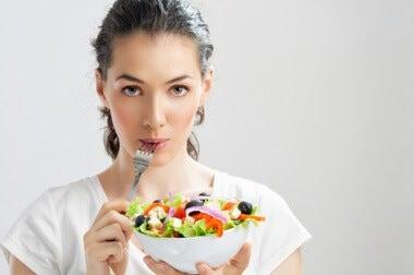Frau isst gesunden Salat um Epigastralgie zu verhindern
