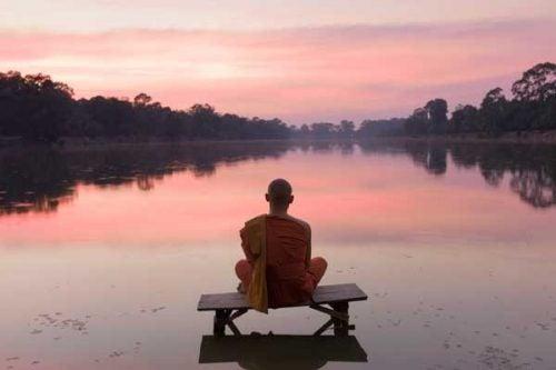 Mönch meditiert und bedankt sich mit Namaste
