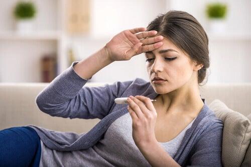 Frau mit Thermometer denkt an Geschlechtskrankheiten