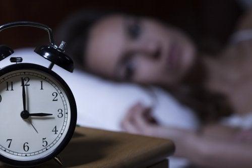 Frau im Bett weiß, dass Diabetes zu Schlafstörungen führen kann
