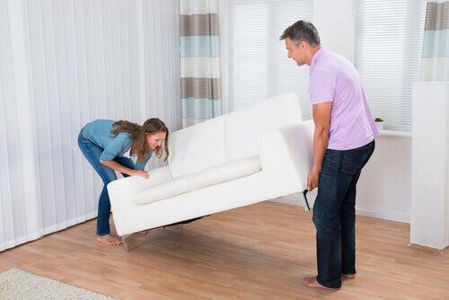 Frau und Mann planen die perfekte Ordnung für Zuhause und platzieren ein Sofa