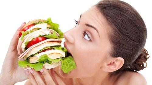 Eine Frau beißt mit Heißhunger in einen Burger, was ein Frühwarnzeichen für Diabetes sein könnte.