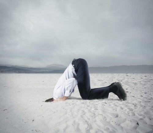 Mann steckt Kopf in den Sand, denn er hat ungelöste Probleme