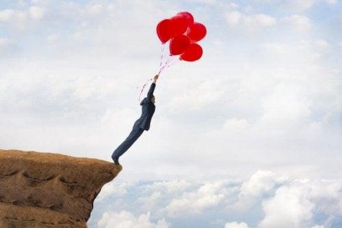 Mann hat ungelöste Probleme und hält sich an roten Luftballons
