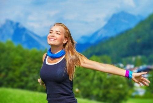 Frau in den Bergen fühlt mehr Energie durch viel Wasser