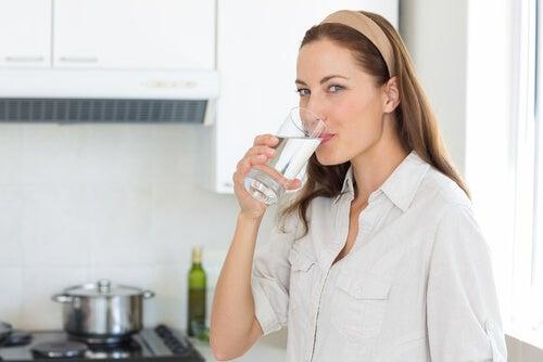 Frau trinkt viel Wasser in der Küche