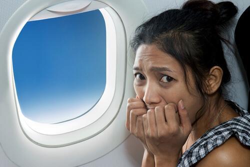 Frau mit einer Panikattacke im Flugzeug
