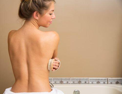 Frau bürstet Haut, um Gewicht zu verlieren