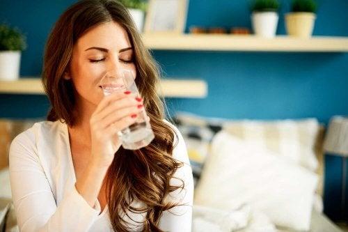 Frau hat stechende Kopfschmerzen und trinkt Wasser