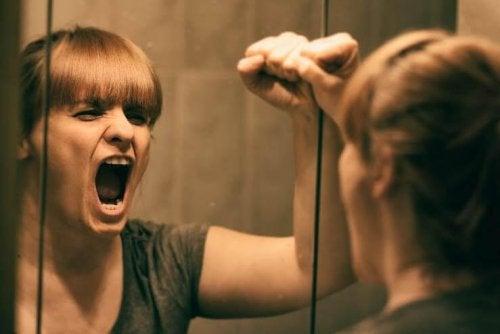 Frau hat emotionales Leid und siehts sich im Spiegel an