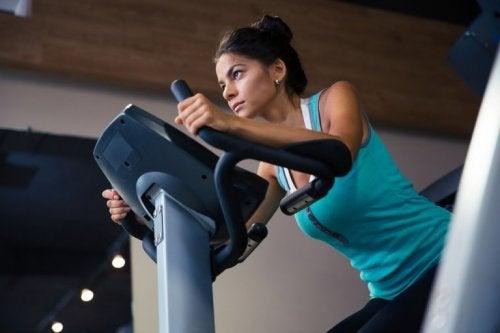 Frau trainiert am Fahrrad für höheren Kalorienverbrauch