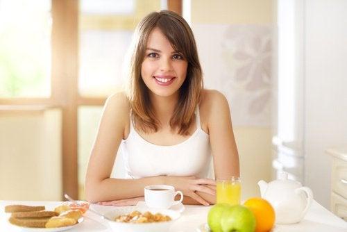 Eine Frau sitzt am Tisch und freut sich auf ein gesundes Frühstück.