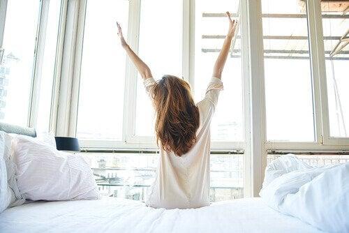 Eine Frau ist gerade aus dem Bett aufgestanden und freut sich auf ein gesundes Frühstück.