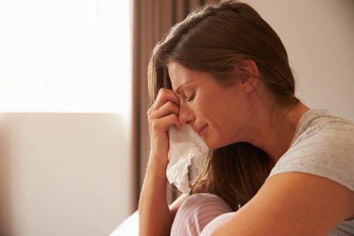 Eine Frau wischt sich mit einem Taschentuch die Tränen aus dem Gesicht.