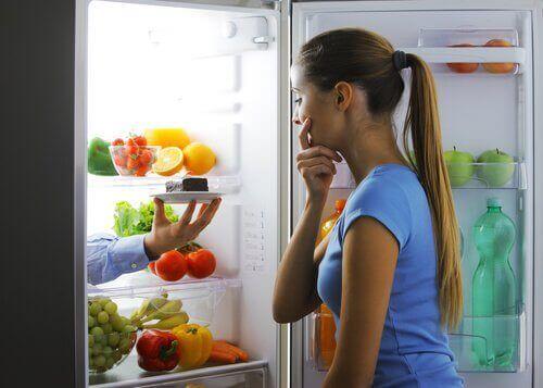 Frau vor dem Kühlschrank isst abends zu viel