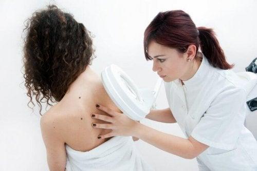 Ein Arzt untersucht Leberflecke