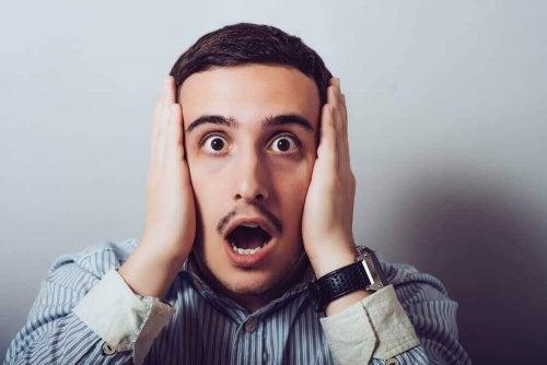 Ein schockierter Mann mit dem Cotard-Syndrom und mit weit aufgerissenem Mund hält sich beide Ohren zu.