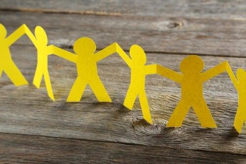 Eine Reihe gelber Männchen aus Papier gebastelt stehen auf einem Holztisch.