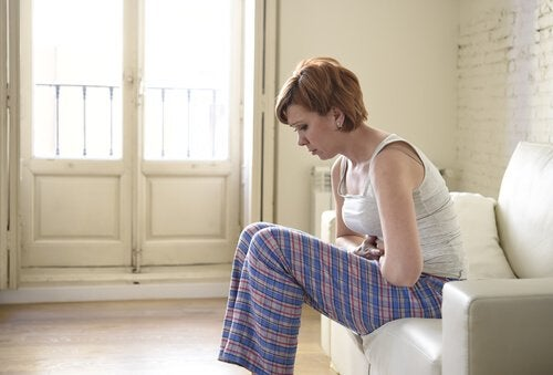 Eine Frau sitzt auf ihrem Bett, nach vorne gebeugt und ihren Unterleib haltend.