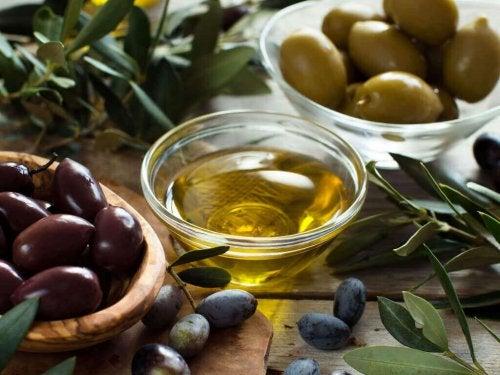 Eine Schale mit Olivenöl steht neben einer Schale gefüllt mit Oliven.