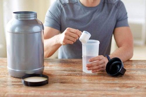 Ein Mann sitzt am Tisch und schüttet etwas Kreatin in Pulverform in sein Getränk.