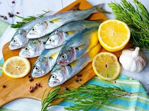 Sieben Fische, voller gesunder Fette, liegen auf einem Holzbrett, umringt von Zitronenschalen.