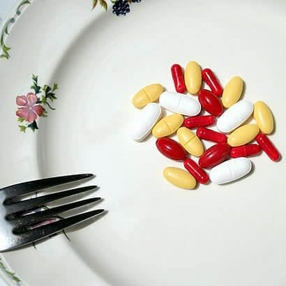 Einige bunte Tabletten liegen auf einem Teller, neben einer Gabel.
