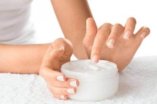 Eine Frau mit gesunden Nägeln hält eine Feuchtigkeitscreme.