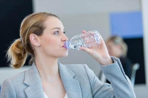 Eine Frau trinkt Wasser aus einer Plastikflasche.