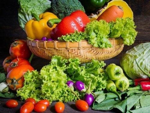 Viele verschiedene Gemüsesorten in und vor einem Korb, wie Paprika, Salat, usw.