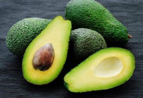 Drei Avocados und eine vierte, aufgeschnittene Avocado sind abgebildet.