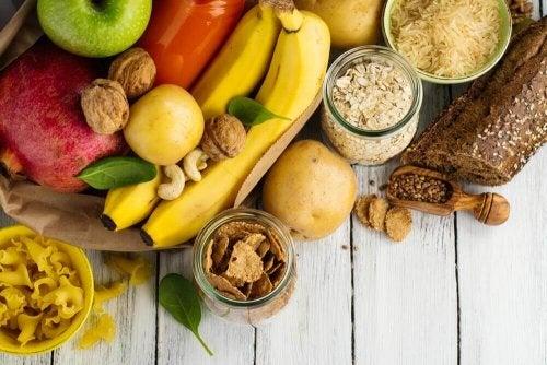 Es sind gesunde Kohlenhydrate abgebildet, in Form von Bananen, Walnüssen, Äpfeln und mehr.