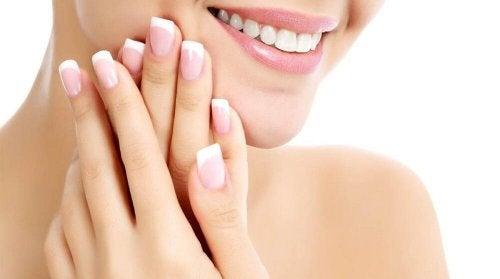 Eine Frau hält sich ihre schönen und gesunden Nägel ans Gesicht und lächelt.