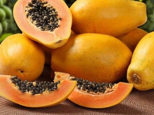 Die gesündesten tropischen Früchte: Abgebildet ist ein Haufen an Papayas, wobei eine davon aufgeschnitten ist.