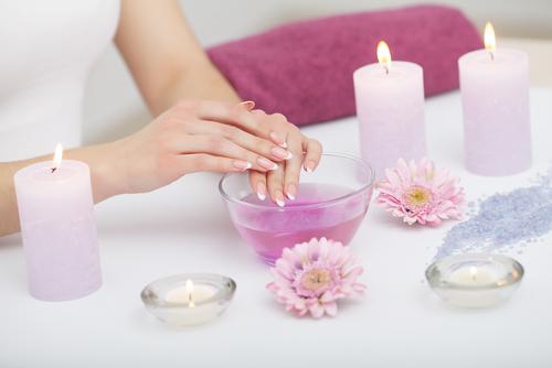 Feuchtigkeitsspendende Flüssigkeit in einer Schüssel, daneben stehen Blumen und Kerzen, während eine Frau ihre Hände am Rand der Schüssel stützt.