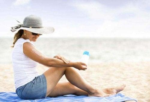 Eine Frau sitzt am Strand und trägt Sonnenschutzcreme auf.