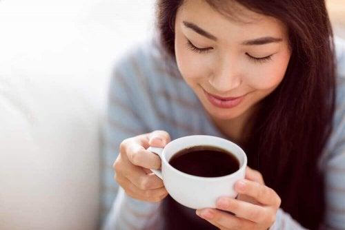 Eine Frau trinkt mit einem zufriedenen Lächeln ein Getränk.