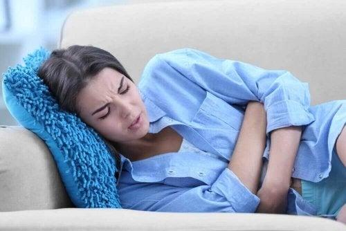 Eine Frau mit Eierstockschmerzen liegt mit schmerzverzerrtem Gesicht auf einer Couch.