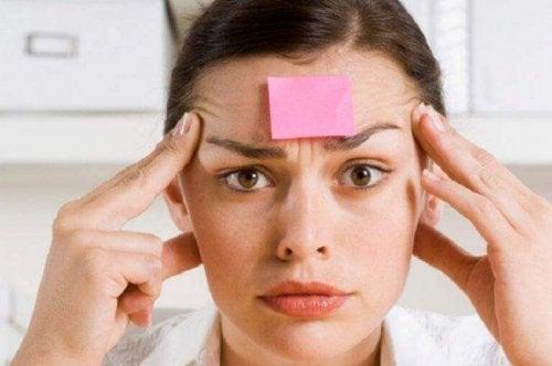 Eine Frau reibt sich die Schläfen, während auf ihrer Stirn ein Klebezettel befestigt ist.