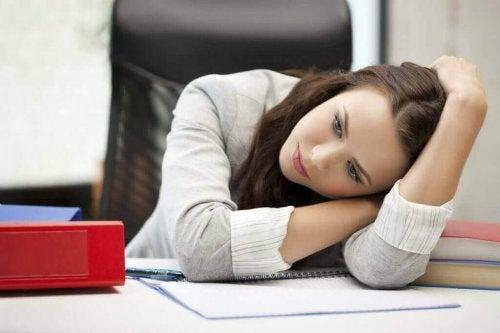 Eine Frau mit Depressionen sitzt an ihrem Schreibtisch.